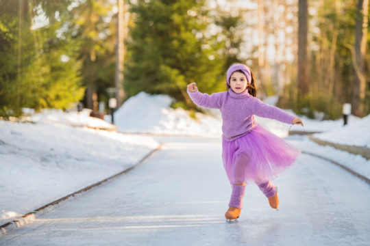 little young girl in a pink sweater and a full skirt rides on a sunny winter day on an outdoor ice rink in the park